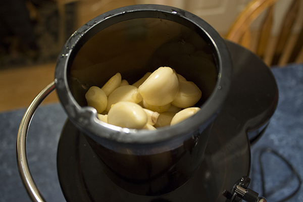 Place Garlic Cloves In The Hopper Of The Juicer