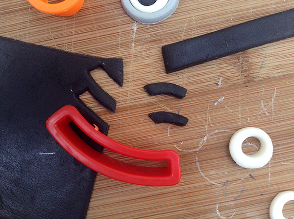 Cut mouth shapes from rolled black fondant to make Minion mouths.